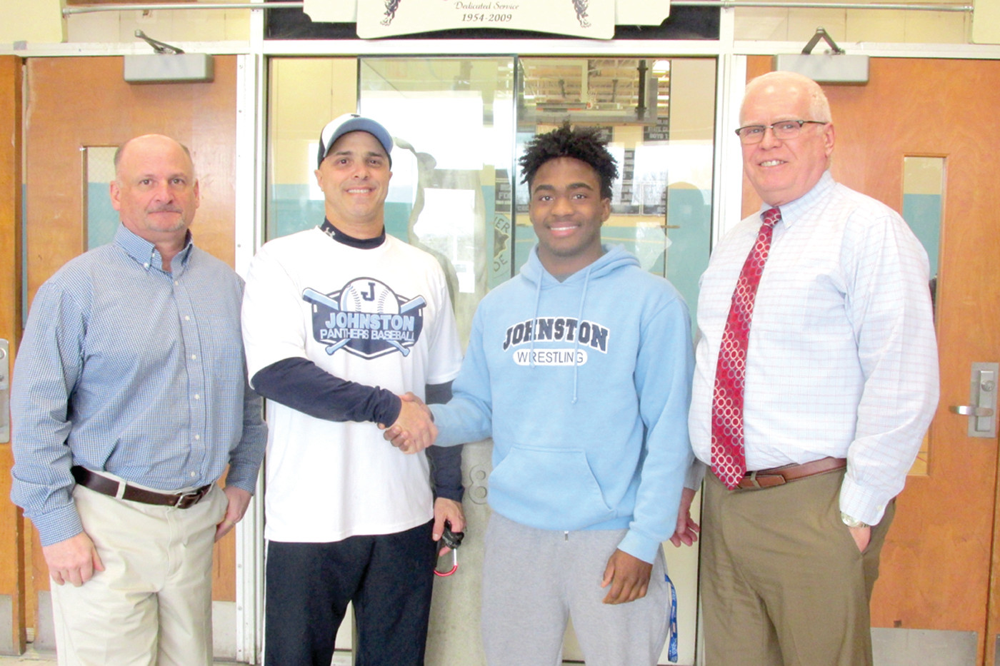 GOLDEN GREAT: Elijah Burgess (third left), a standout scholar-athlete and senior at Johnston High School, receives congratulations from Head Football Coach Joe Acciardo upon his selection for the RI Chapter of the National Football Foundation and College Hall of Fame's Golden Dozen Award. He's joined by Athletic Director Keith Cory and Principal Dennis Morrell. (Sun Rise photo by Pete Fontaine)