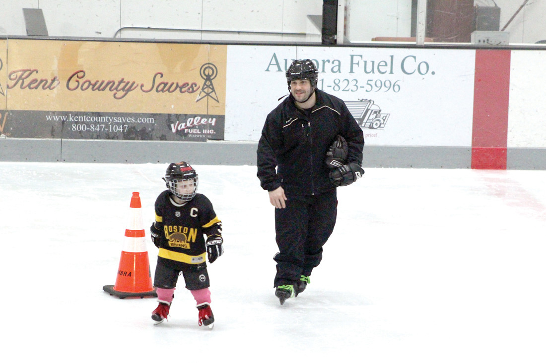Knights coach Mike Shannon skates with one of the kids at the Learn to Skate, Learn to Play Program.