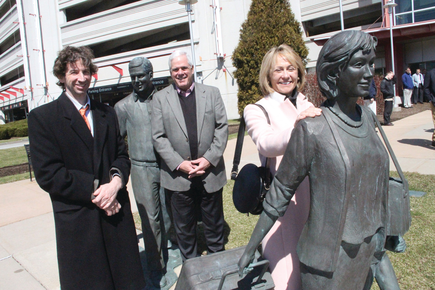 FAMILIAR FACES: Sculptor Chris Kane (left) was commissioned in 2000 by Jim Skeffington to do a sculpture outside the Red Beam Garage. Skeffington got Karl Sherry and his wife Kathy to model for the work that took Kane two years to complete. No, the Sherrys didn't spend two years posing, but the Sherrys were at the airport Thursday for the reopening of the garage and to stand alongside their immortal lookalikes for a quick photo.