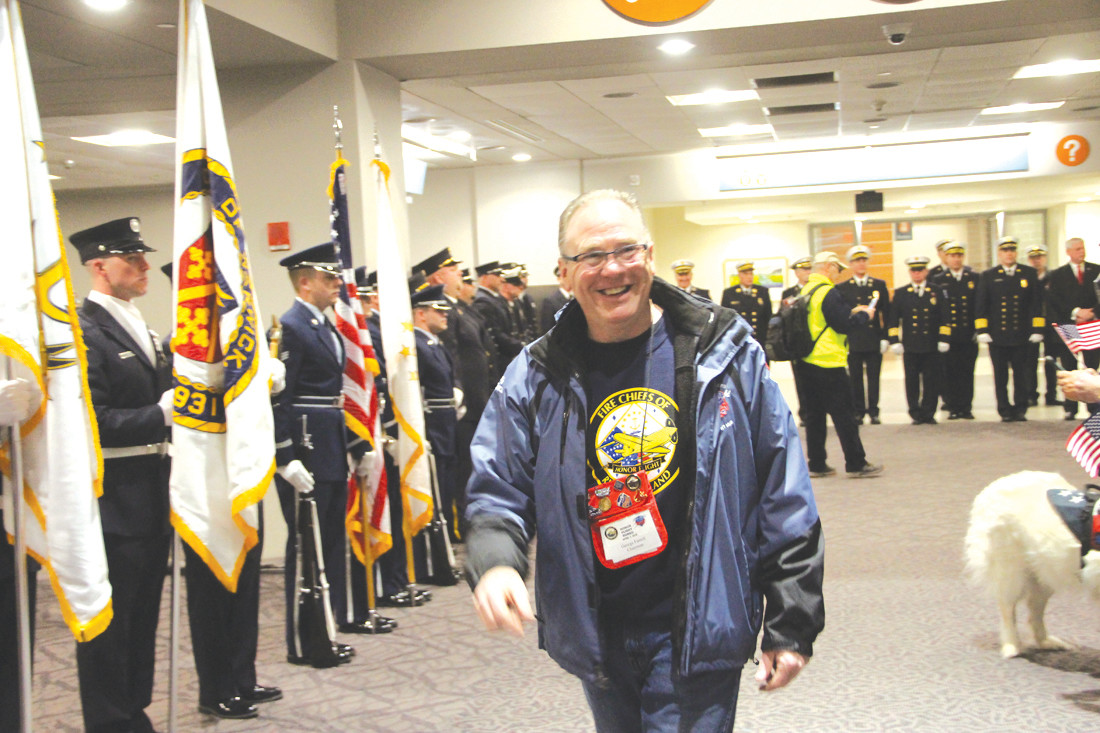 LEADING THE WAY: George Farrell, who heads up the Rhode Island Fire Chiefs Association Honor Flight, flashes a smile of appreciation to the many who turned out to honor veterans participating in Saturday's flight.