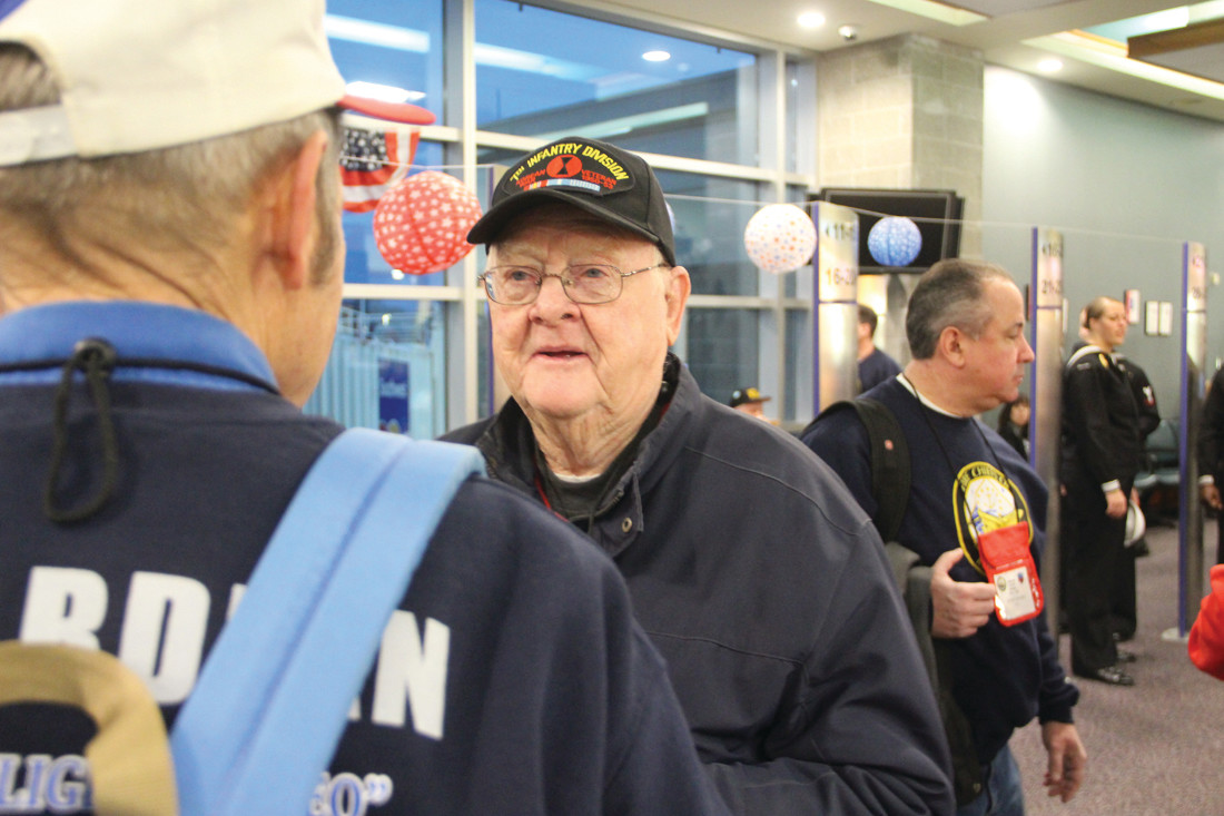 GETTING THE SCOOP: Korean War veteran Clyde Bennett and his guardian, John Pierson, chat before boarding the flight to Washington.