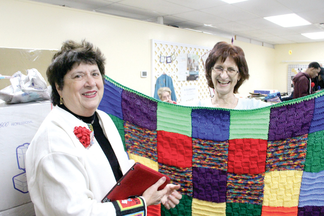 "THAT SECURE FEELING: Project Linus Rhode Island collected hundreds of handmade blankets Saturday to be given to children in hospitals and shelters. Here coordinator Martha Sholes admires the crochet blanket of Michaela Mueller. What makes the blankets special, says Sholes, is that they ""have heart."""