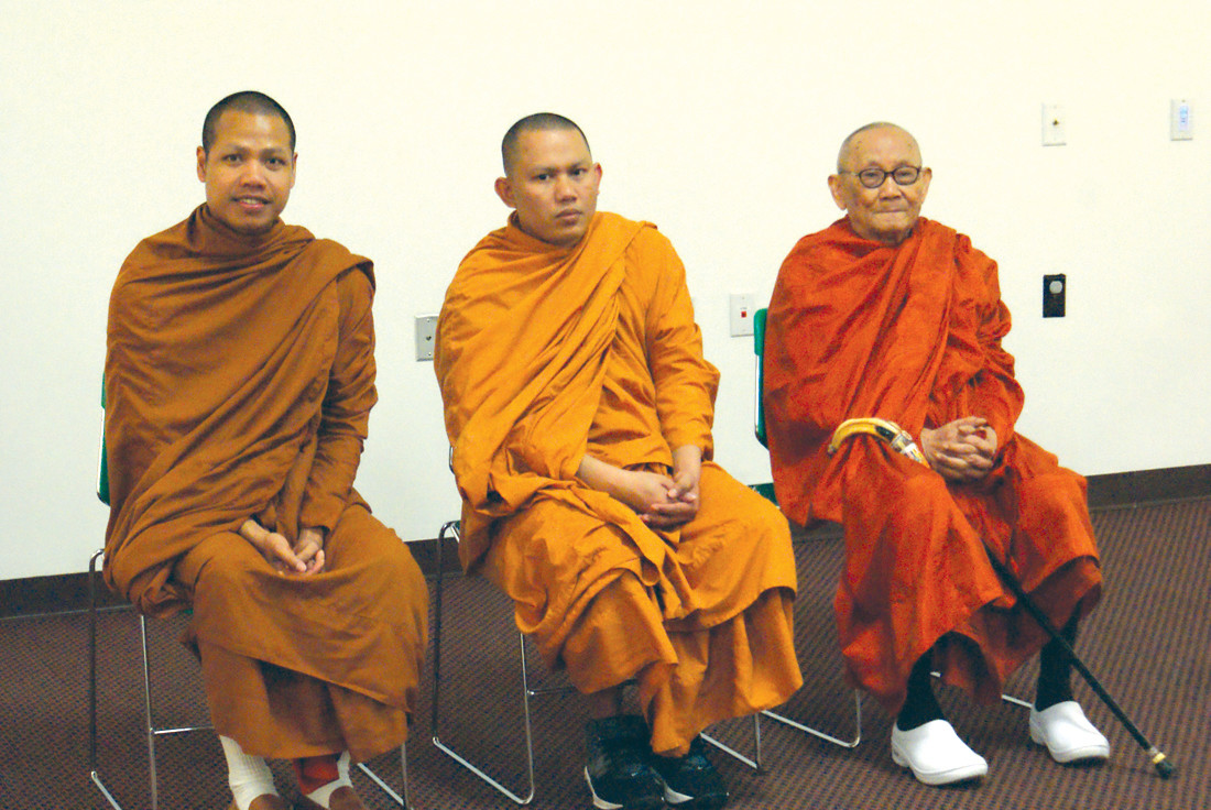 PRIOR TO PRAYER: Just before they led the attendees at the Cranston Public Library in prayer, all three Buddhist from three different temples posed for a photograph. From left to right are Lin Somonnorom (Buddhist Center of NE), Sopheap Penh (The Cranston Buddhist Temple) and Chik Prum (Thormikaram of RI).