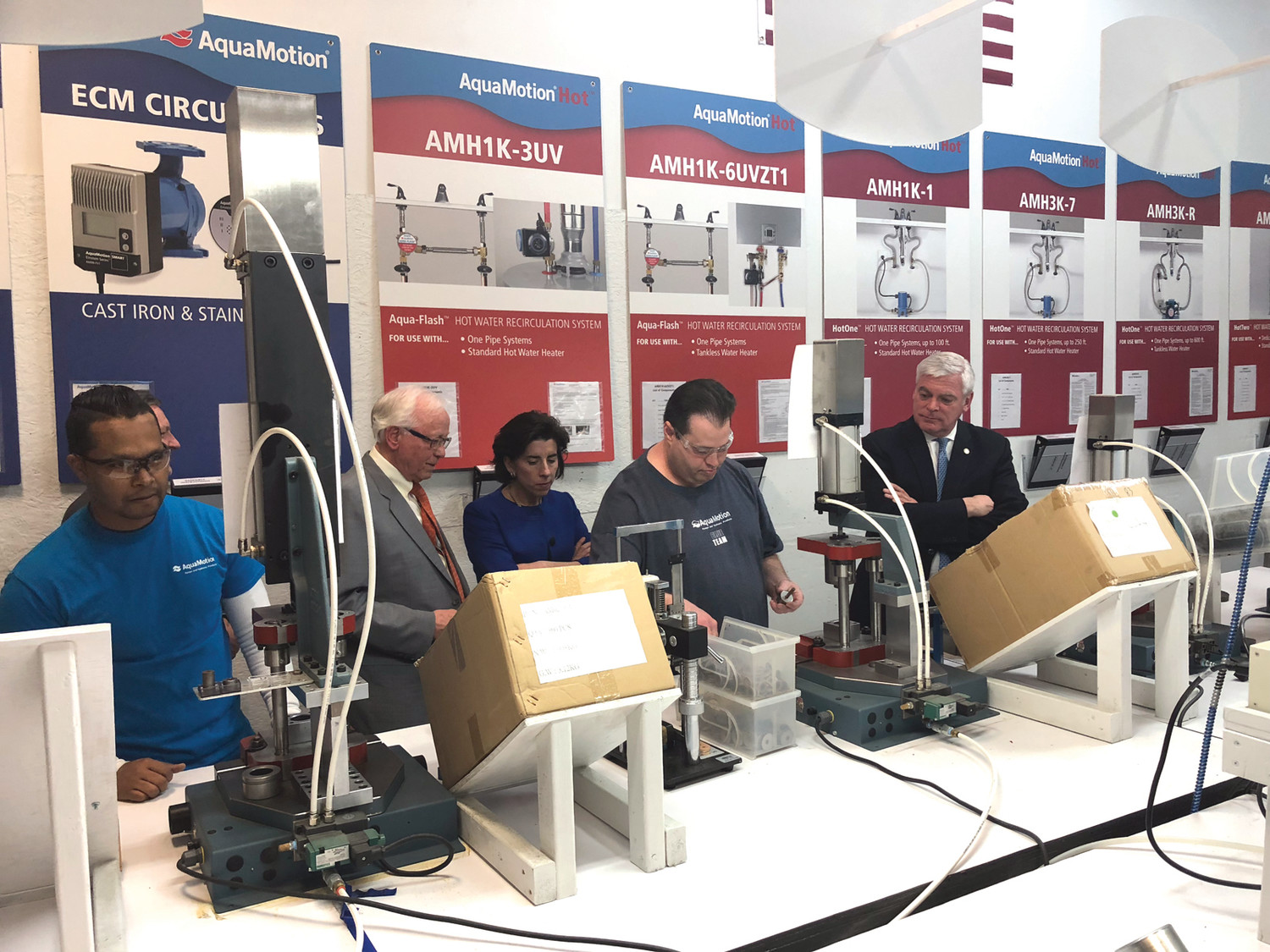 ON THE LINE: Governor Gina Raimondo, AquaMotion president Hans Kuster and Mayor Scott Avedisian observed as workers assembled plumbing products for AquaMotion from the initial assembly to the final testing.