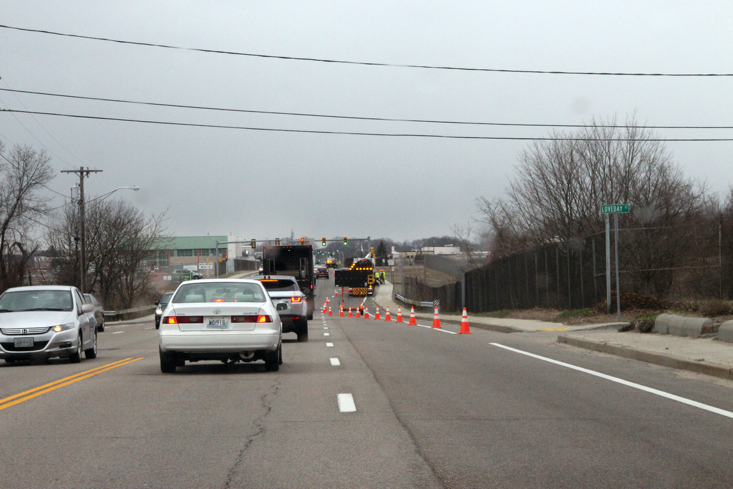 WORK AHEAD: Cones and a flashing arrow direct motorists to merge into a single lane on Airport Road Tuesday as Rhode Island Department of Transportation crews cleaned drains.