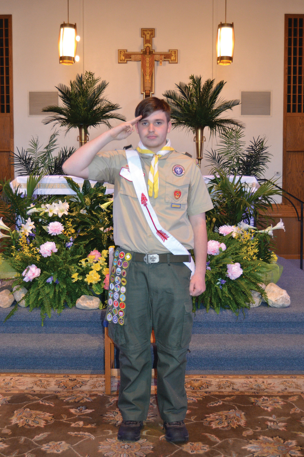 SCOUT SALUTE: Newly inducted Eagle Scout Patrick Young of Troop 20 Johnston leads his troop during his Eagle Scout celebration last Sunday.
