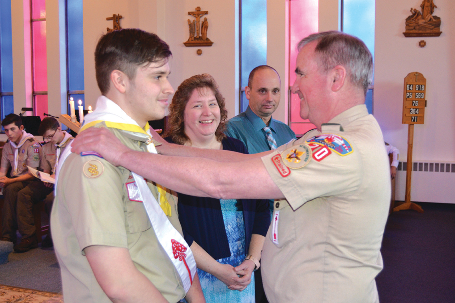 DUBBED IN: Troop 20 Scoutmaster David Curtin performs the traditional shoulder pat on Patrick, signifying his advancement to the rank of Eagle.