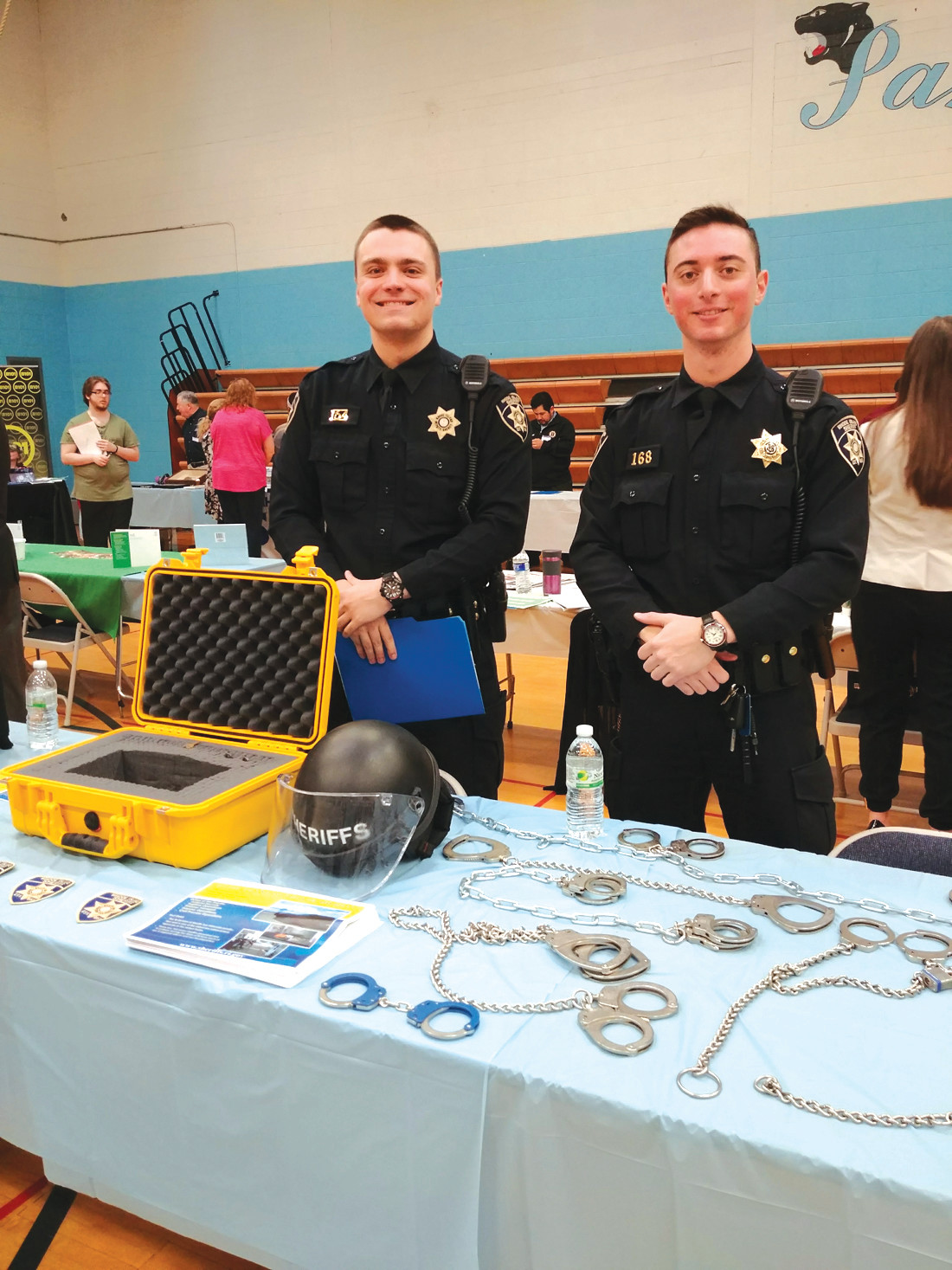IT MUST BE HANDCUFFS: Many adults and students alike were drawn to the table set up by RI Family Court Sheriffs Ryan Anderson and Gian Bianchi, which had a large display of various types of handcuffs and other equipment needed in their profession.