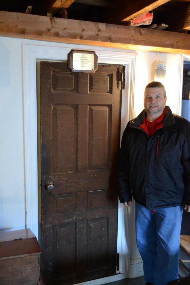 DOOR TO THE PAST: Pawtuxet Ranger Commander Ronald Barnes stands by the door which once provided entry to the Sabin Tavern, the local spot where colonial patriots planned to board and burn the HMS Gaspee, a significant event leading up to the Revolutionary War. (Warwick Beacon photos)