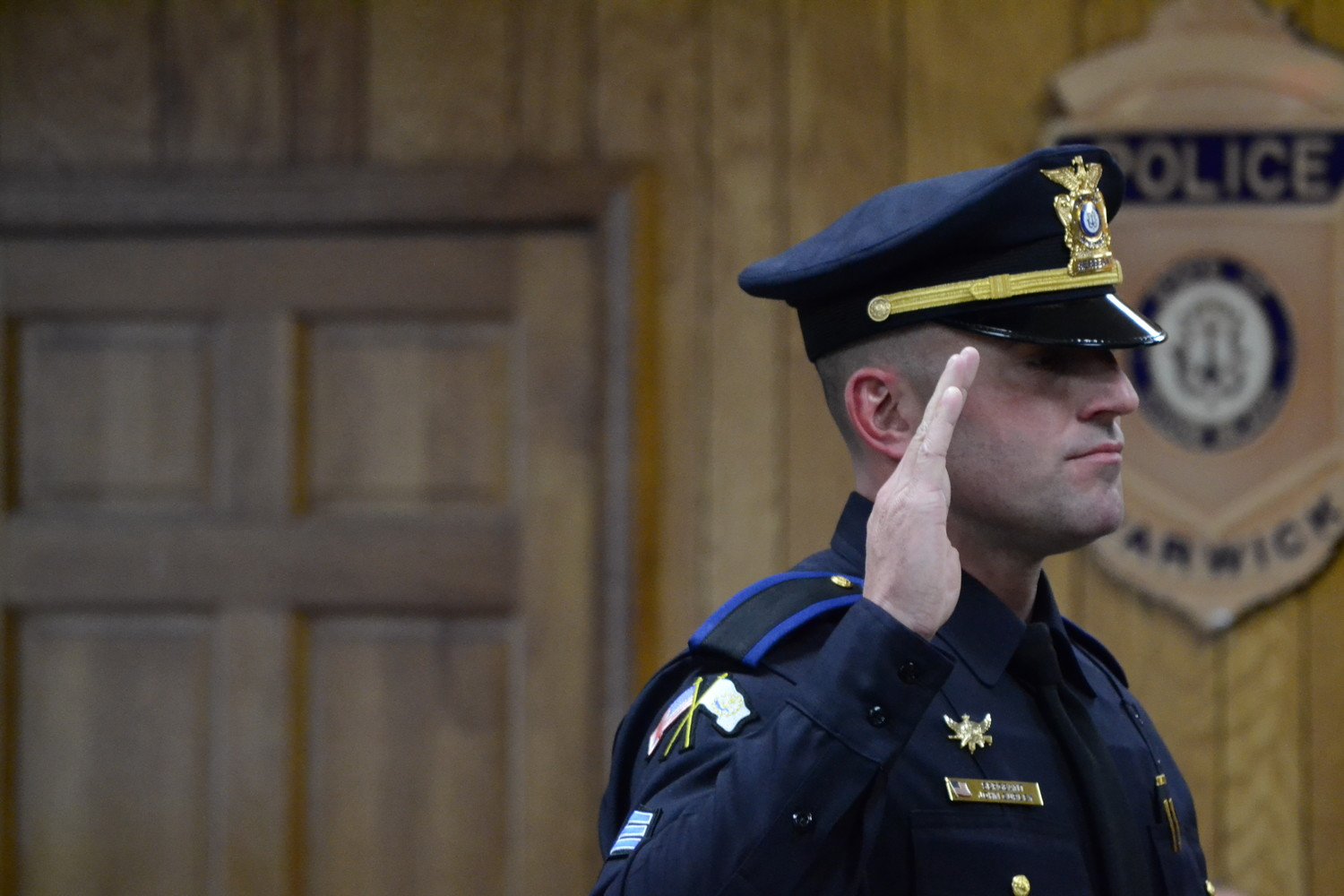 PROMOTED: John Curley while being sworn in as a new sergeant in the Warwick Police Department. He was pinned by his wife, Mallory.