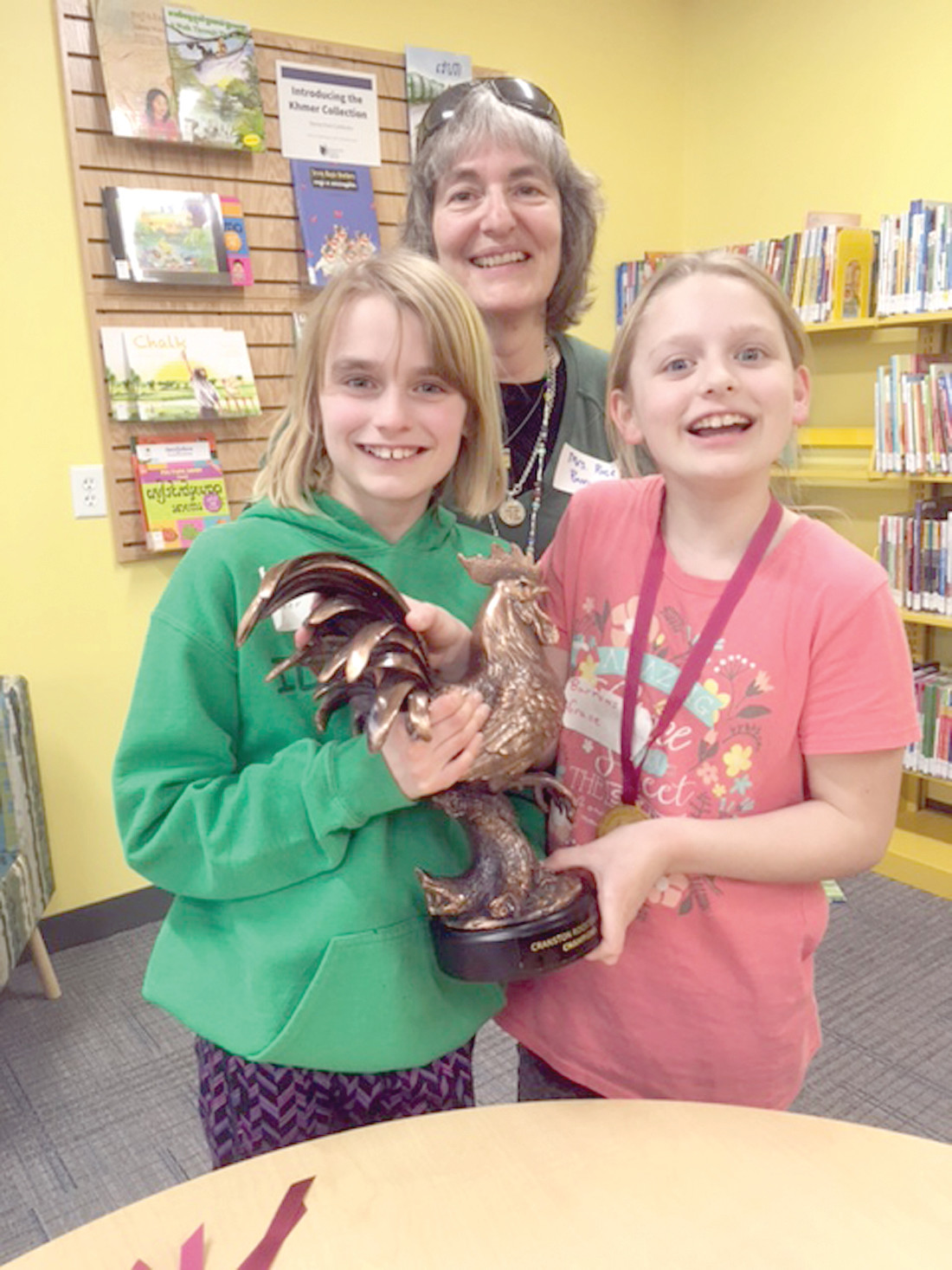 TROPHY COMES HOME TO ROOST: Getting their hands on the first Rooster Games Trophy are Barrows students Kara Bush and Grace Michaelson alongside Barrows School Librarian Sue Rose.