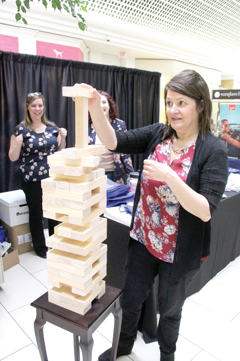 HOW HIGH WILL IT GO? Jennifer Lema of Picerne Real Estate that operated a booth at the fair balances a block in the giant Jenga that had mall visitors reaching for heights before the structure tumbled.