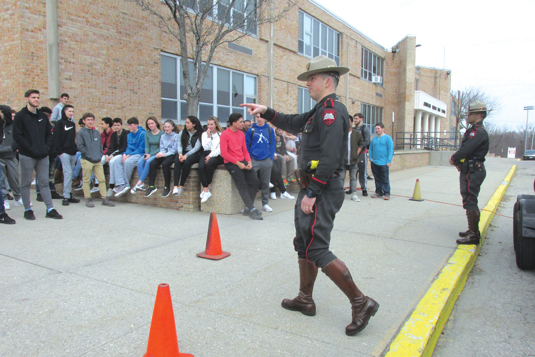 TROOPER'S TALK: Rhode Island State Trooper LJ Fiorenzano fields questions during a recent visit to JHS that included demonstration what happens in a car crash roller over when a passenger or passengers are not wearing seat belts.