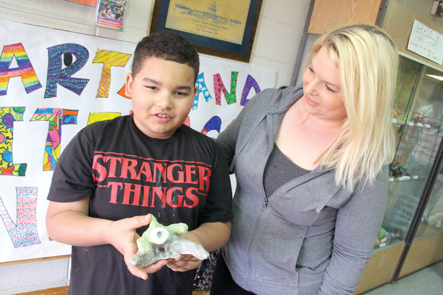 STRAIGHT FROM THE DISPLAY CASE: Fourth grader Alex Rodrigues shows off the sculpture he made to his mother, Melody Rodrigues, during the Arts and Literacy Night at Oakland Beach School.