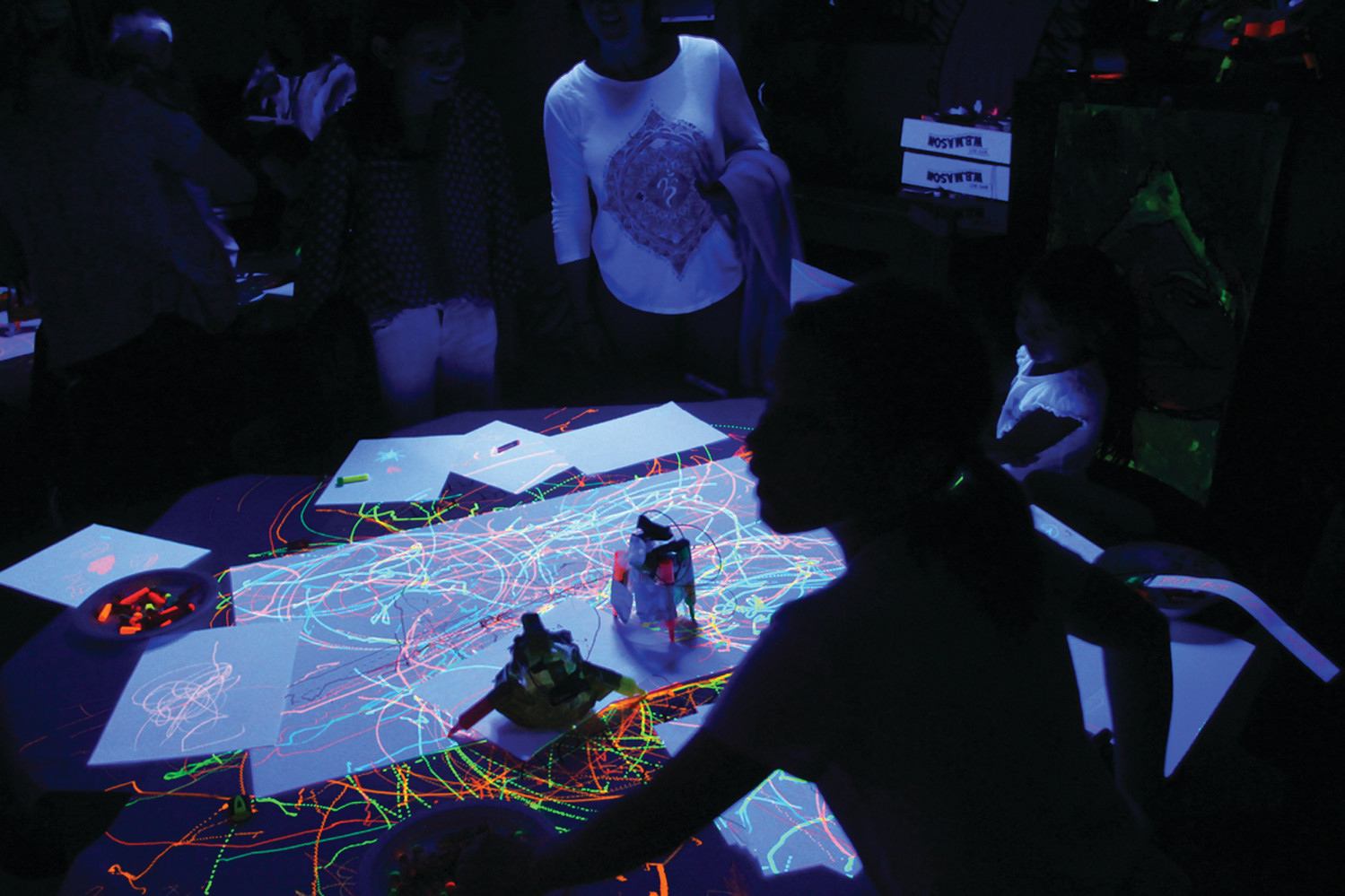 "BOT ART: Robots did their creative thing in the eerie glow of ultraviolet light. Students and parents joined in the experience creating their own ""glowing"" drawings."