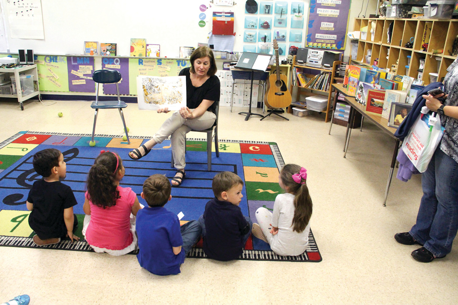 BOOKS PUT TO MUSIC: Teacher Tricia Kammerer read stories to students and their parents, putting the words to music.