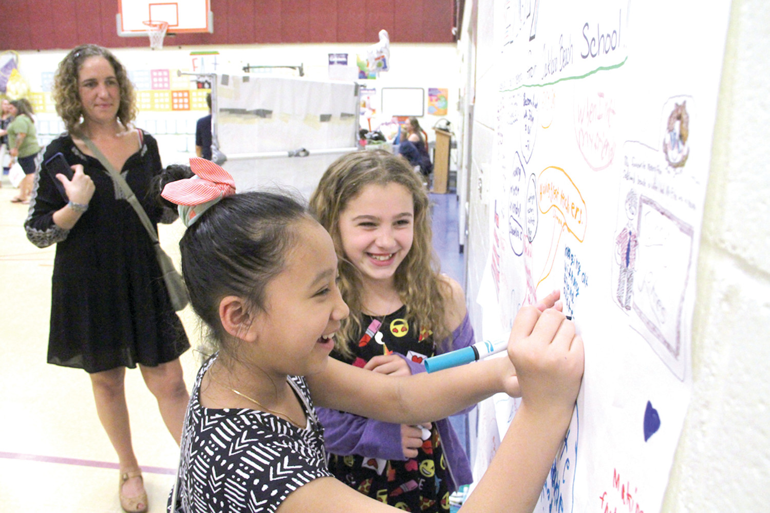 RECORDING MEMORIES: Third grade friends Kamilah Wosczyna and Jayleen Mony were thrilled to write on the memory wall.