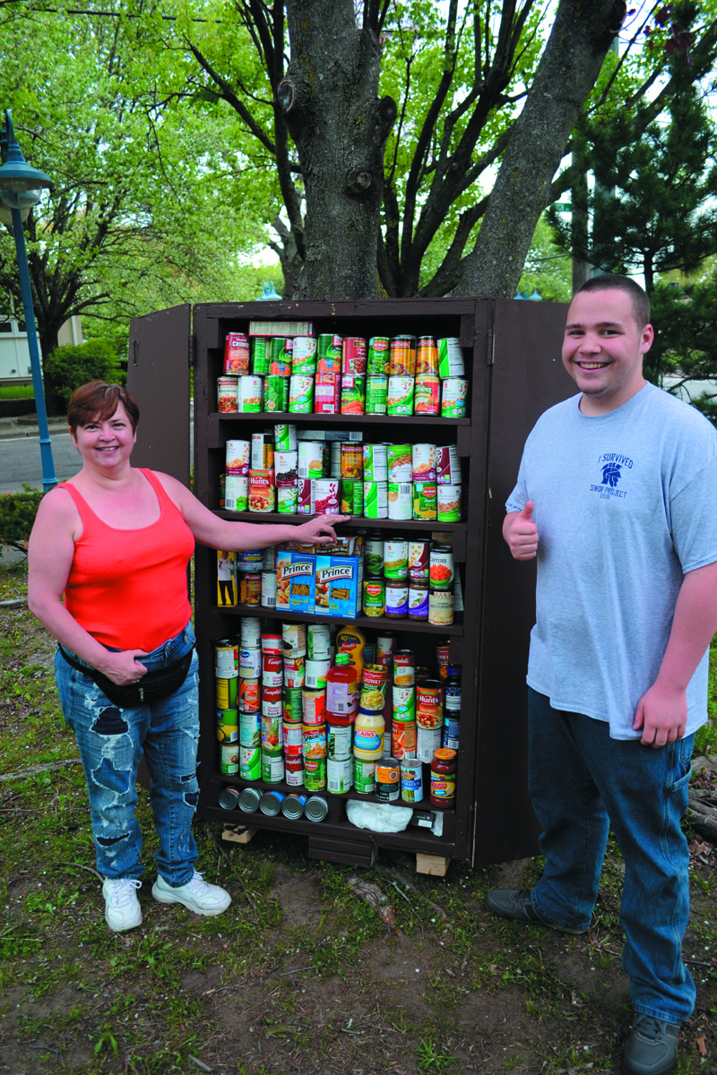 CAN-DO ATTITUDE: Vincent and Robin Arsenault in front of the can cupboard that Vincent built for his Toll Gate senior project. Residents have helped stock the cupboard completely full.