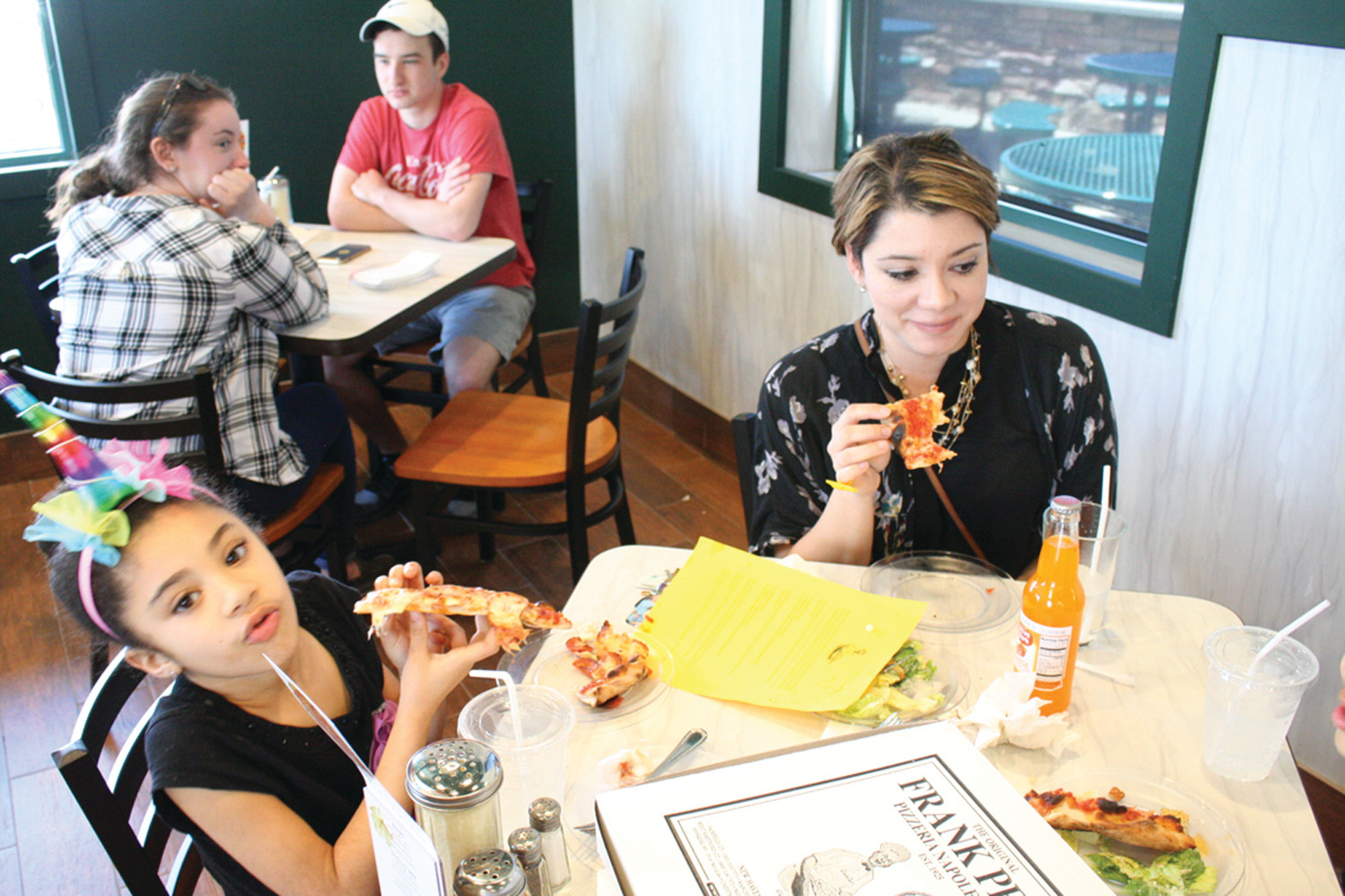 PIZZA OVER SCHOOL: Jennifer Valley brought her daughter, Lyric De Jesus, and son, Jonathan De Jesus, to the free pizza day Friday afternoon at Frank Pepe's, saying it was tough to pass up the tasty deal. The family lives in Warwick.
