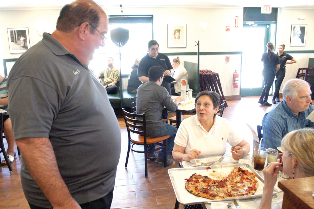 MEETING THE COMMUNITY: Gary Bimonte, who is the co-owner of Frank Pepe's and the grandson of Frank Pepe, speaks with the patrons of their new location on Friday afternoon as they gave out free dine-in pizza.