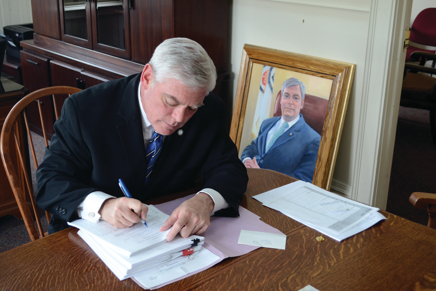 FINAL BUSINESS: Mayor Scott Avedisian signs the last stack of docket items to appear on the next City Council agenda. His official portrait sits behind him, waiting to be hung in City Hall.