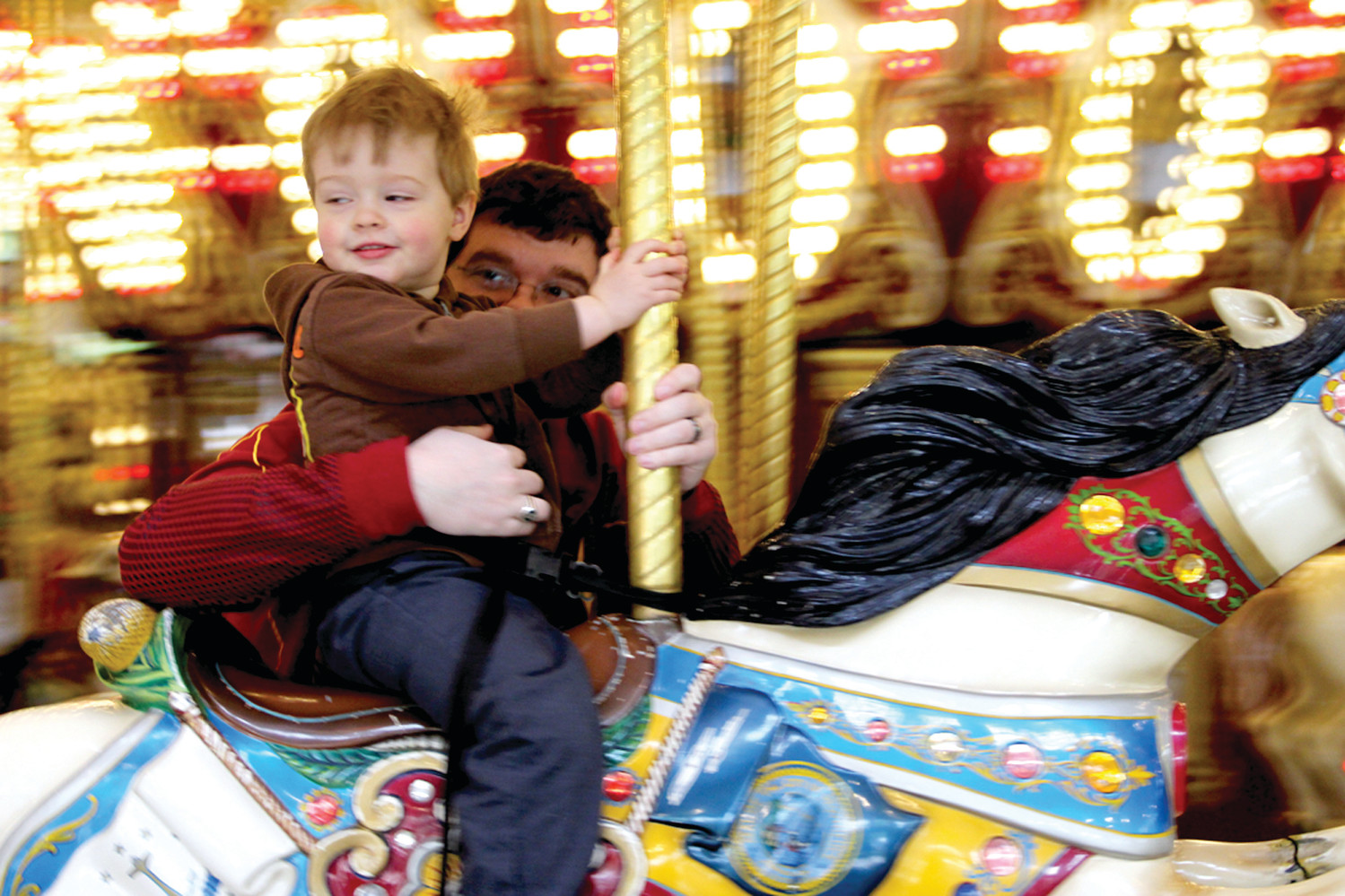PART OF THE FUN: With his father Joshua holding on Silas Davis takes a spin on the carousel.