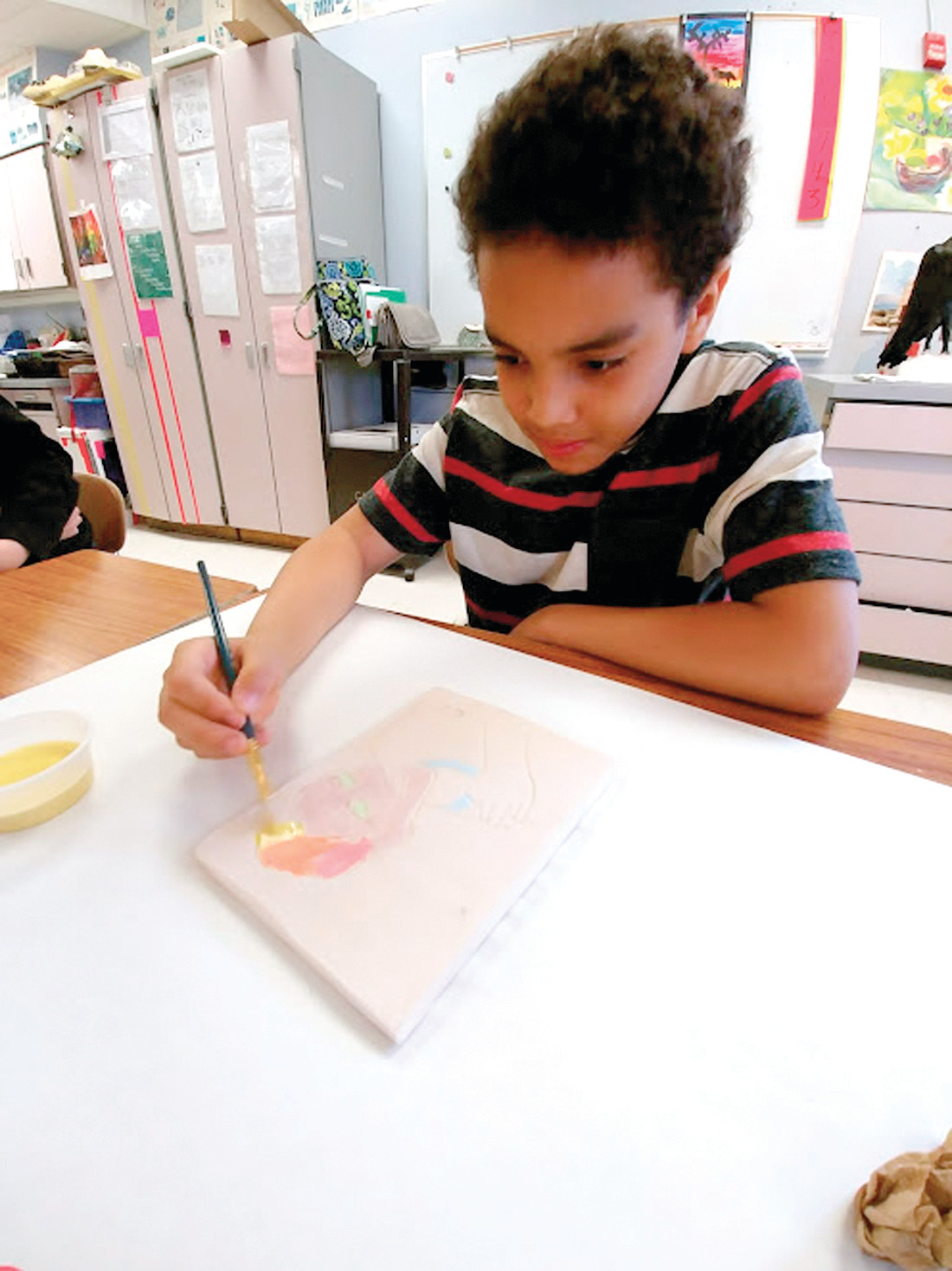 HOW IT ALL BEGAN: The pop art projects began with a photograph taken of each student from Edgewood. The photos were then traced and transferred on to a slab of clay prepared by the students from East.