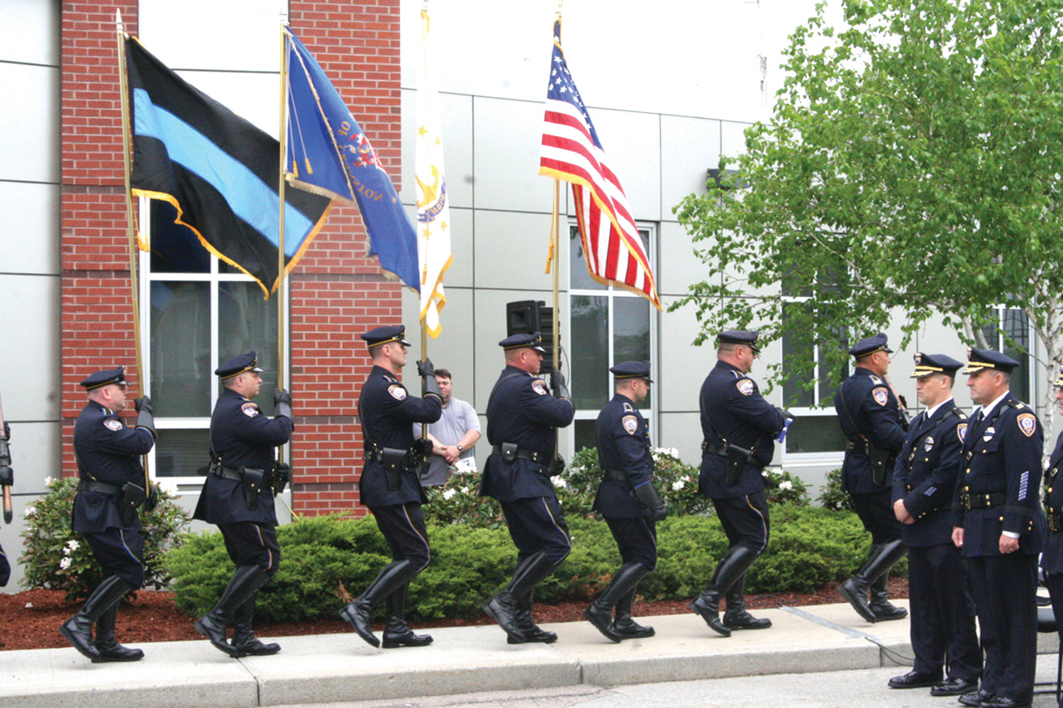 HONORING THE FALLEN: Cranston Police Officers march with the flags outside of the police station on Garfield Avenue Tuesday morning to honor fallen police officers from the city, state, and country.