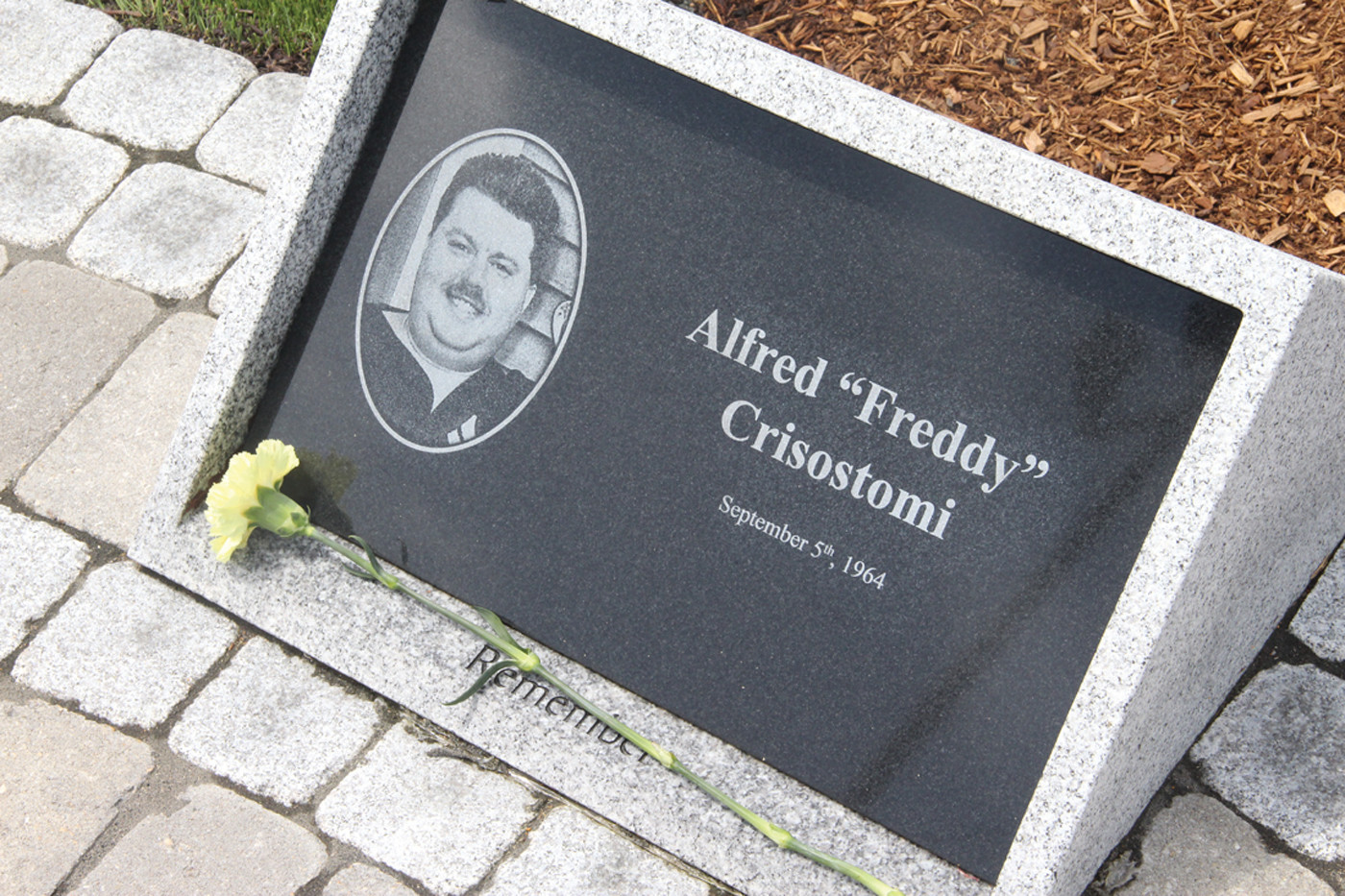 "ONE OF 100 ANGELS: With a flower at his stone, Alfred Crisostomi is one of the 100 who lost their lives in The Station nightclub fire on Feb. 20, 2003. Alfred, ""Freddy"" as he was known, was the fiancé of fire survivor Gina Russo, who heads the Station Fire Memorial Foundation."