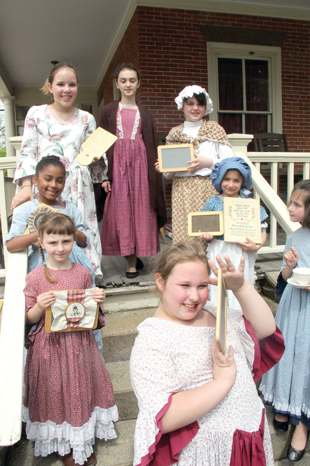 THEY HAD TABLETS: Yes, colonial students had tablets, although they surely weren't called Chromebooks or iPads back then. Here, the students from the Pawtuxet Girls Academy gather on the steps of the Bank Café to describe the classroom of the colonial era.
