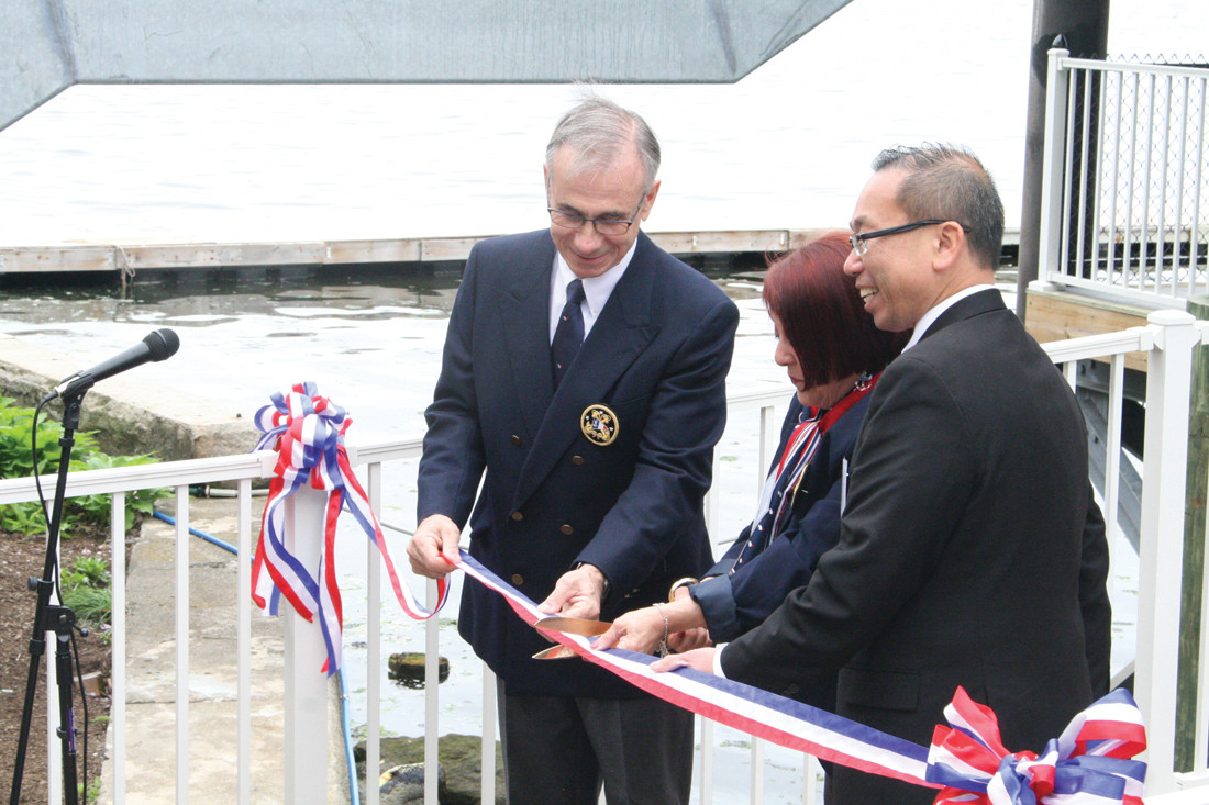 A LONG-AWAITED RIBBON CUT: Wayne Kizerian, a former commodore and current Edgewood Yacht Club building committee chair, cuts the ribbon with current commodore Flo Spenard and Cranston Mayor Allan Fung.