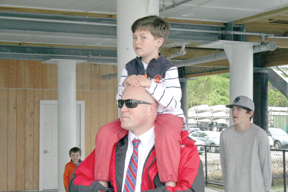 GETTING A BETTER VIEW: Tyler Parkhurst sits atop his father Craig's shoulders on Saturday morning to get a view of the cannons being fired off by the Pawtuxet Rangers to commemorate the re-opening of the Edgewood Yacht Club. The Parkhurst's live in Warwick, and Craig has made a career in the boating industry.