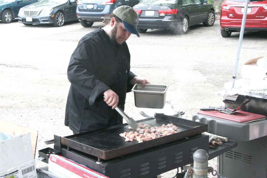 A SAILOR'S BREAKFAST: Michael Devolve, one of the club's full-time chefs, prepares the bacon for the club breakfast that was part of the day's activities.