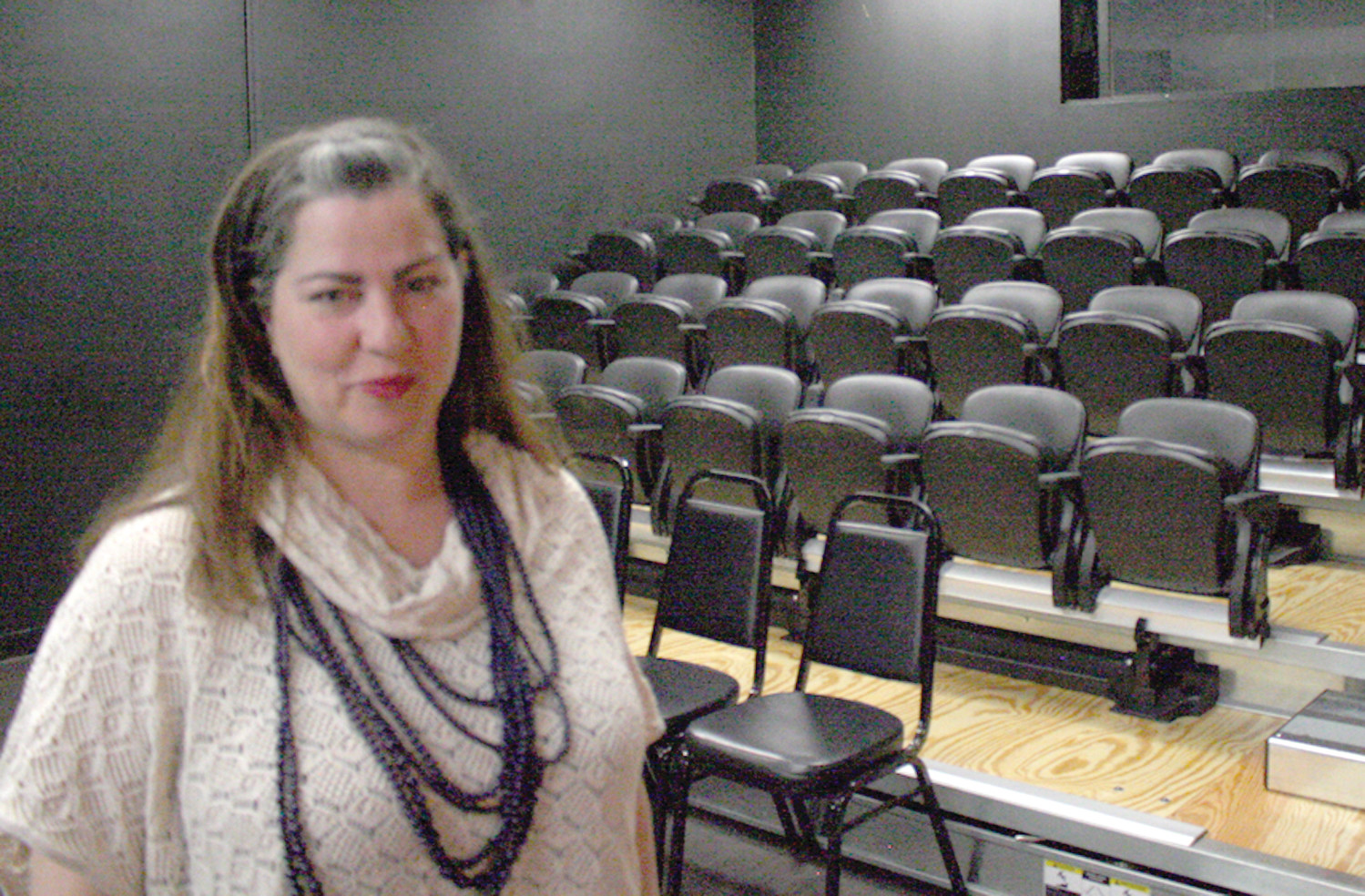 HOME MOVIE THEATER: Elaine McKenna-Yeaw shows the newly done movie theater seats, which holds 50 people and has a projector/screen as well as open floor space for theatre productions.