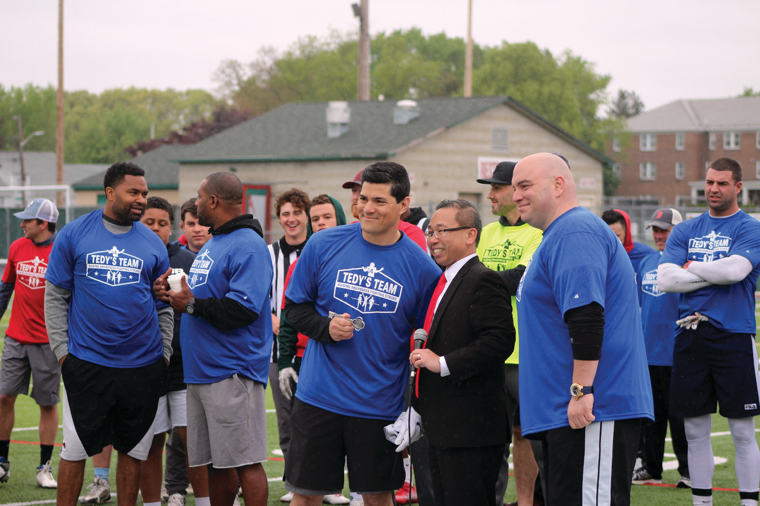 KEY TO THE CITY: Former Patriot great Tedy Bruschi (left) accepts the key to the city of Cranston from Mayor Allan Fung (center) and City Council President Michael Farina (right) on Saturday at Cranston Stadium.