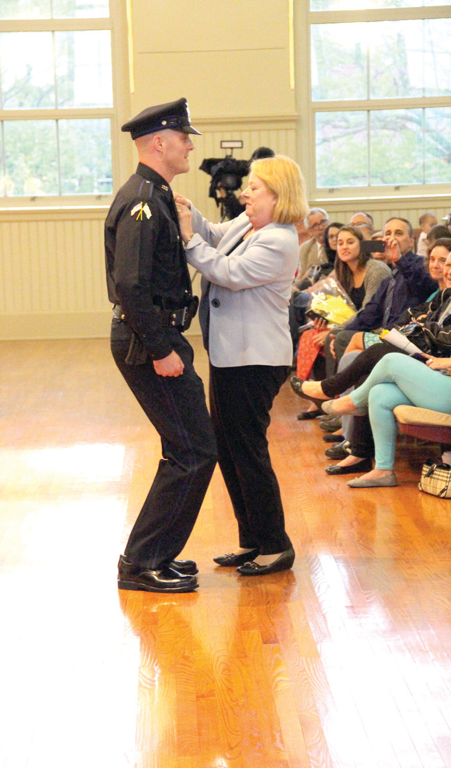HE ALMOST HAD TO KNEEL: Probationary officer Ryan Shibley had to stoop in order for his mother, Carol, to pin on his badge.