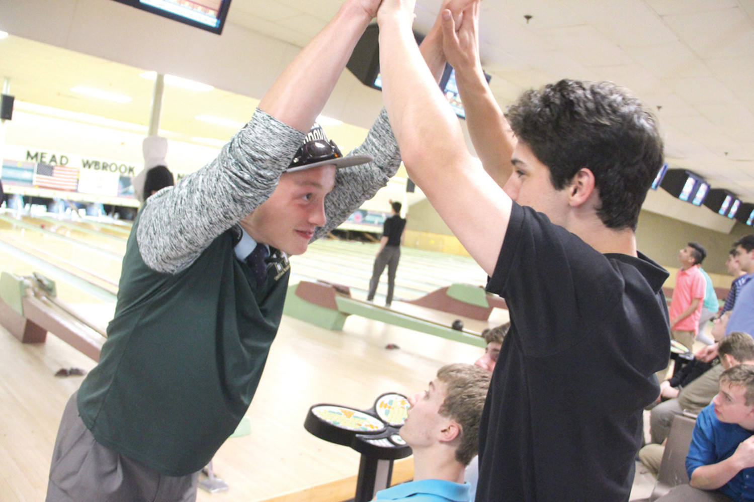 CELEBRATION: Steve Baker and student mentor Brian Schattle share a double high five after Baker knocked out 8 pins.