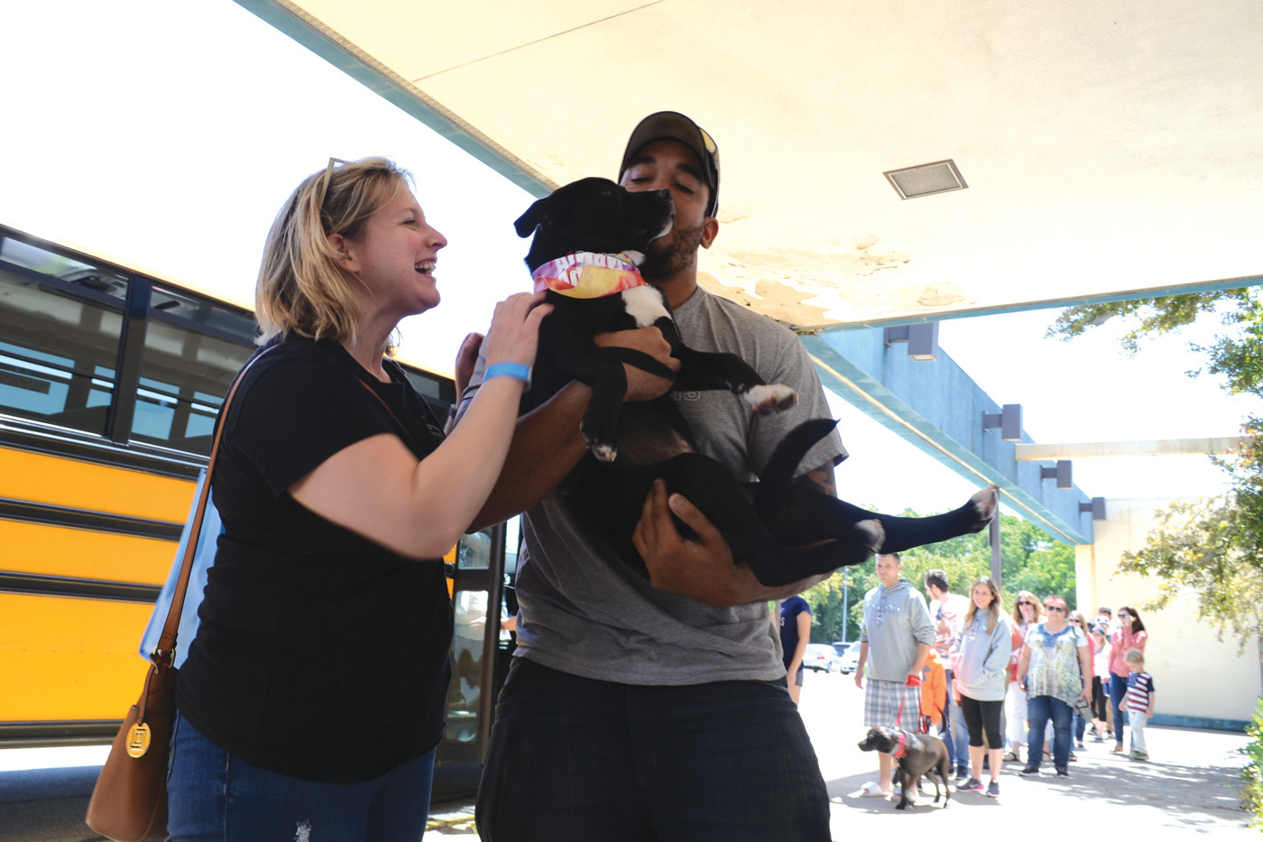 NEW FAMILY: Therysa Zimmer and Earl Jackson were all smiles as they stepped off the shuttle from Balise at the Ann & Hope parking lot, where parking had to be arranged due to the size of the event, with their new forever friend Pearl.