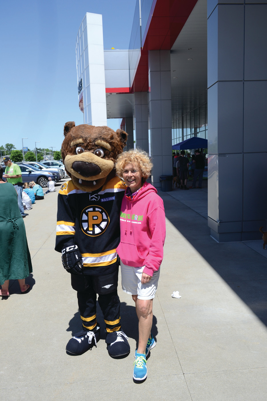 QUITE A SHOW: Louise Anderson Nicolosi, founder of Always Adopt, poses for a photo with P-Bruins mascot Samboni at the Super Dog Adoption Day event in Warwick on Sunday. There were also food trucks and doggy treat vendors throughout the dealership grounds.