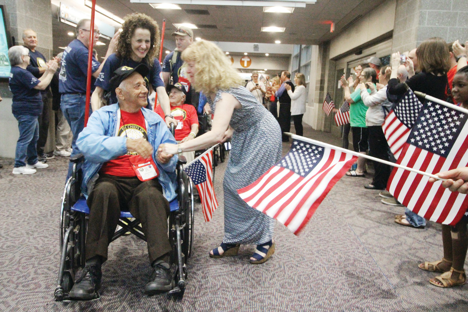 THEIR HERO: WWII Navy veteran Richard Fazzio, 94, being wheeled by Woonsocket Mayor Lisa Baldelli-Hunt, gets a warm reception as he and 23 other veterans on Saturday's Honor Flight arrive at Green Airport.