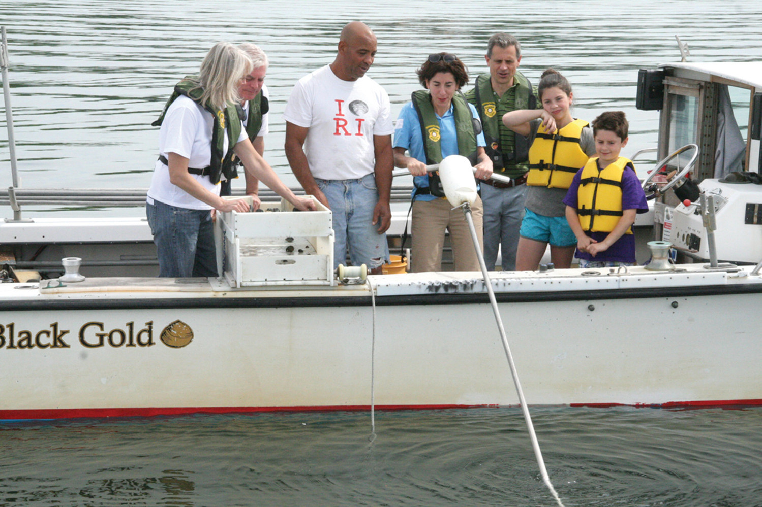 In 2016, under the direction of Jody King, Gina Raimondo tries her hand on the bull rake as Janet Coit, MAyos Scott Svedisian, Andy Moffit and their children, Cecilia and Thompson, watch. Asked what impressed her about the experience, Raimondo said how King's livelihood is dependent upon his catch, one clam at a time.