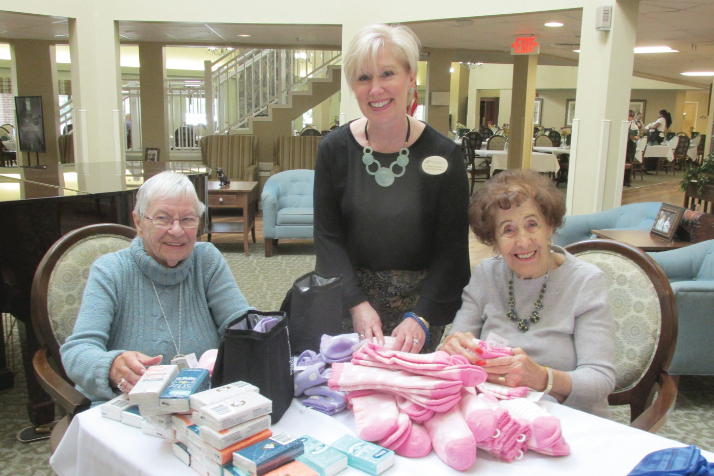 HELPING HANDS: Dawn St. James (center), Sales & Marketing Manager at Brookdale Pocasset Bay, is all smiles and joined by residents Maria Patonio and Rita Gariety during Tuesday's filling of the Blessing Bags.
