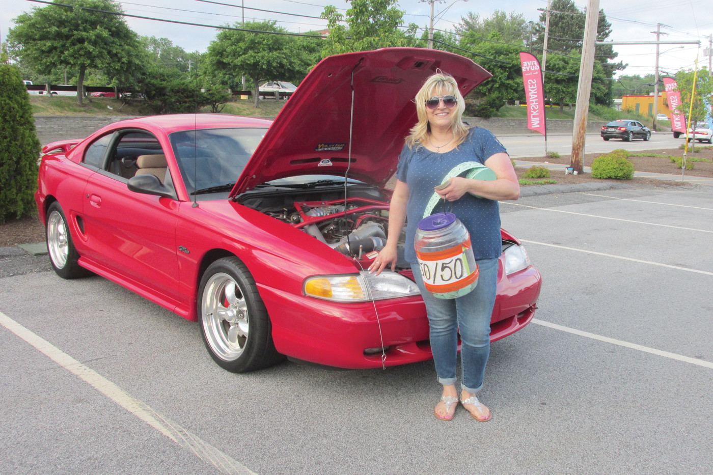 VALUABLE VOL: Tina Marie Brodeur is all smiles as she stands by her red 1998 For Mustang and holds the 50/50 raffle container and tickets that she has volunteered to head up for the JSM's 2018 Cruizin' for a Cause.