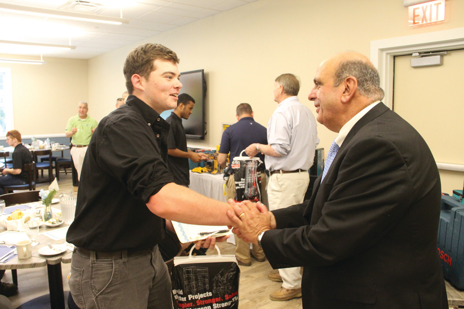 IN THE LINEUP: Acting Mayor Solomon joined representatives from the Rhode Island Building Officials Association in congratulating scholarship recipients. Here he shakes the hand of Andrew Fredericks.