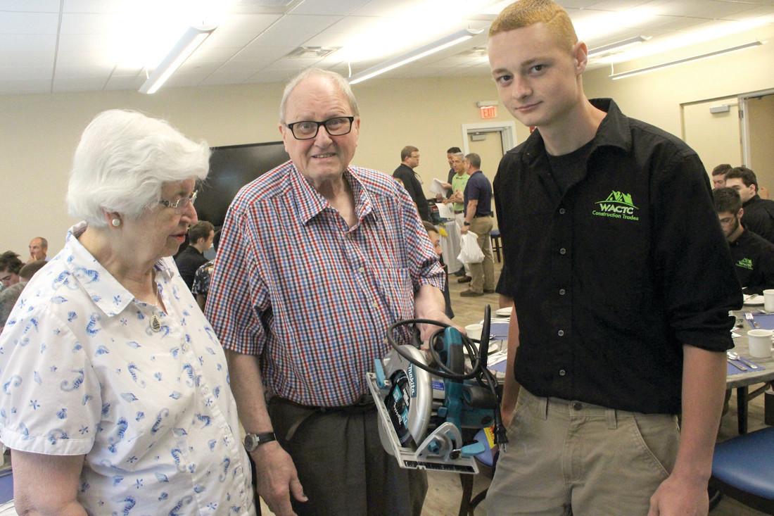 A CUT ABOVE THE REST: Carol and Sam Netcoh of NETCOH Sales talk with Austin Machado of the WACTC. NETCOH provided scholarships so Machado could acquire tools like the saw he is holding.
