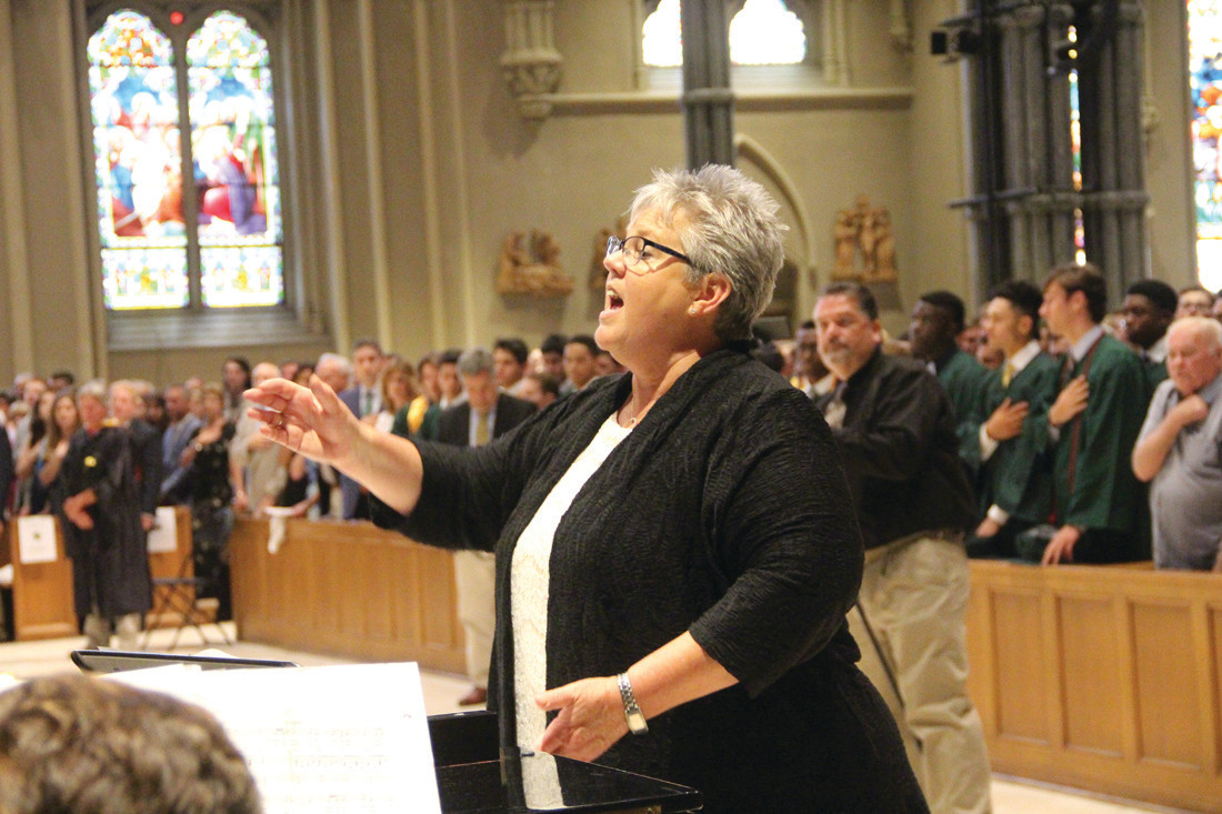 SONG TO INSPIRE: Mary Jo Gambardella, director of vocal music, leads the Young Men's Chorus in the performance of the national anthem.