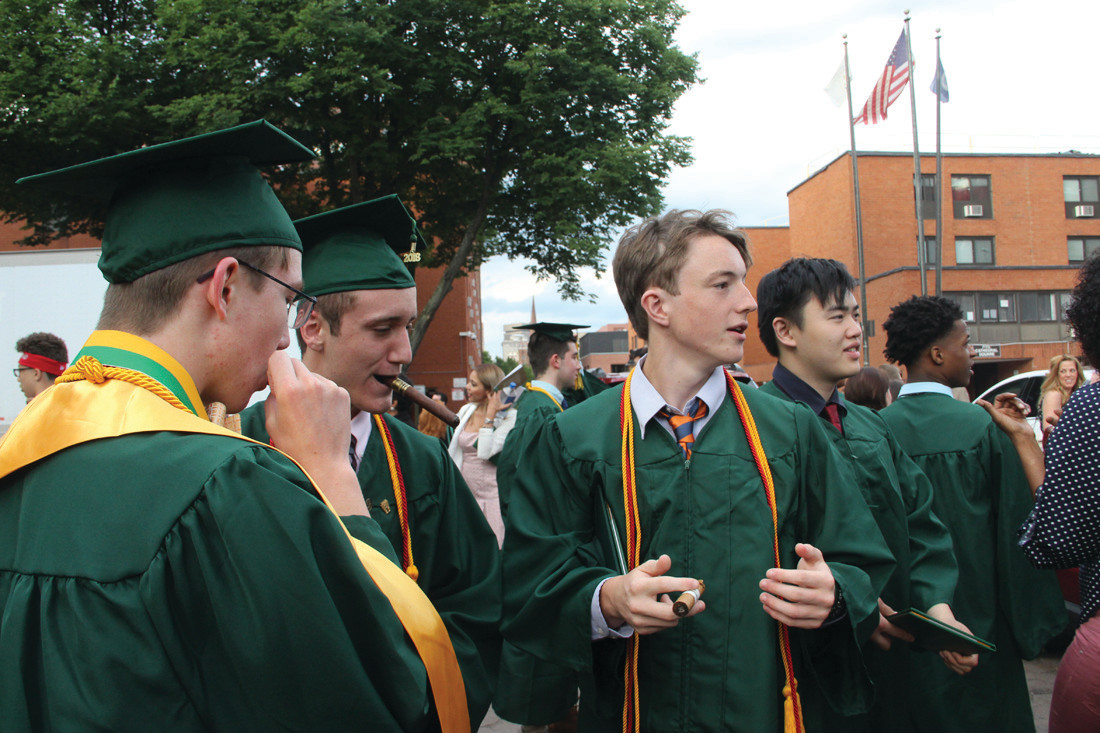 TIME TO LIGHT UP: Hendricken graduates prepare to light up cigars following graduation ceremonies Friday evening.
