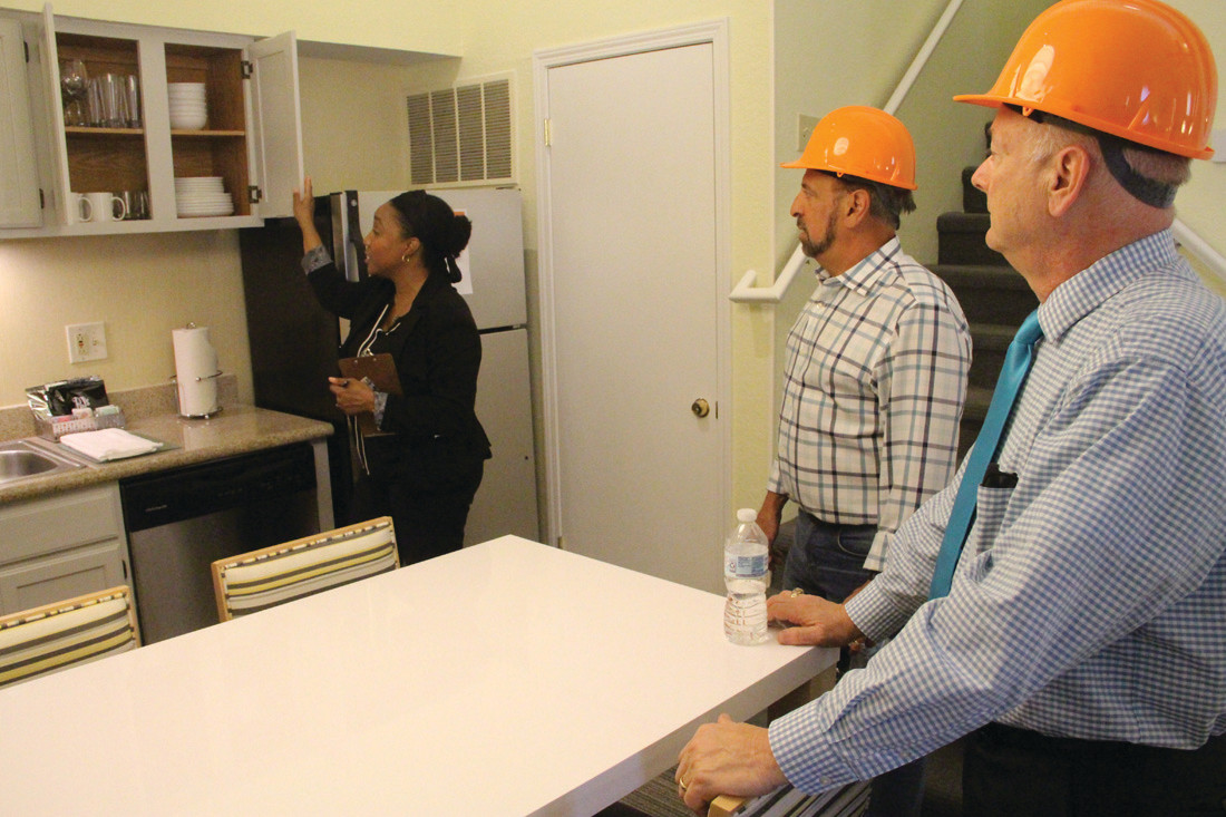 WHAT IT HAS TO OFFER: Sonesta director of marketing Erika Lucas shows off the amenities of a unit to Carmine DeLuca and Dennis Labossiere during Thursday's tour.