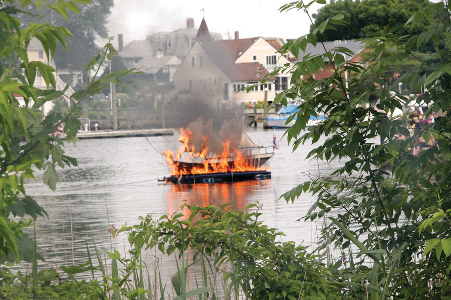 ABLAZE: To the delight of spectators, the Gaspee burns in Pawtuxet Cove.