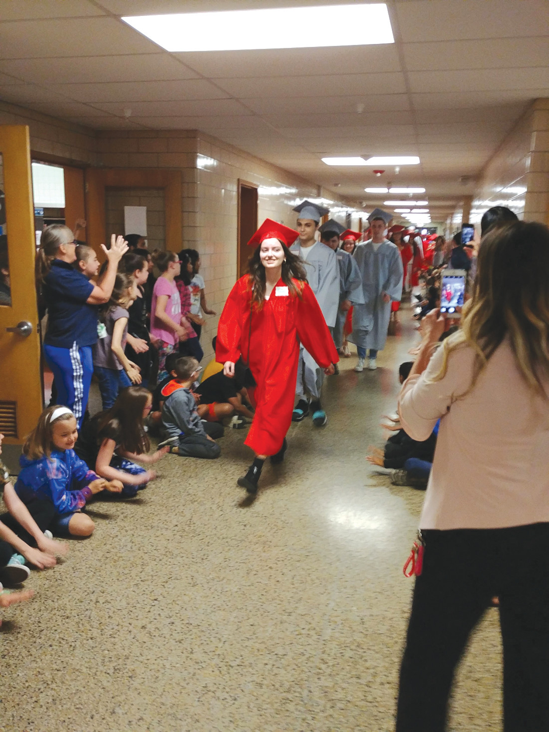 CELEBRITIES FOR A DAY: The seniors may not have been prepared for such a welcome, as the younger students at each school cheered, clapped and held up personalized signs and posters for the graduates.
